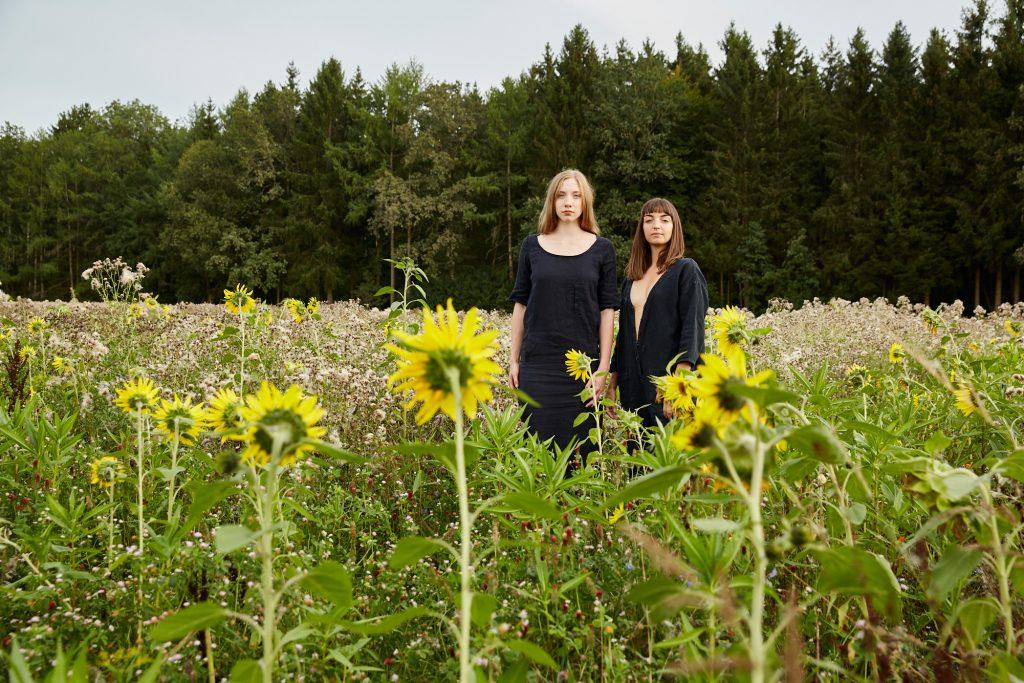 zwei frauen in sonnenblumenfeld