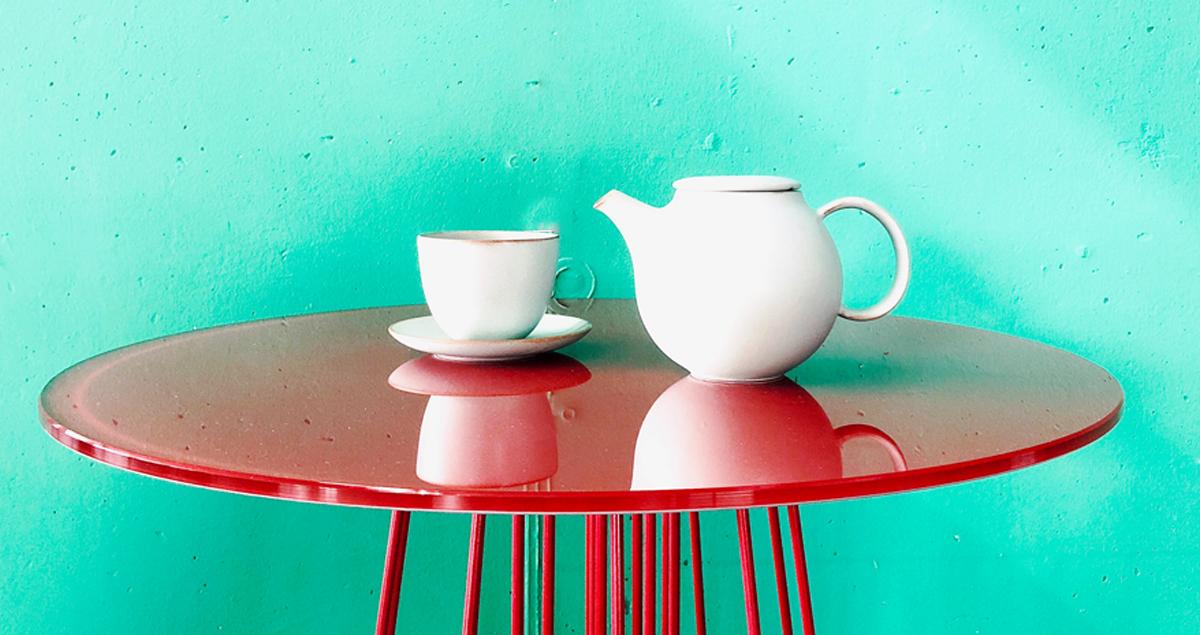 Teekrug auf rotem Tisch vor grüner Wand